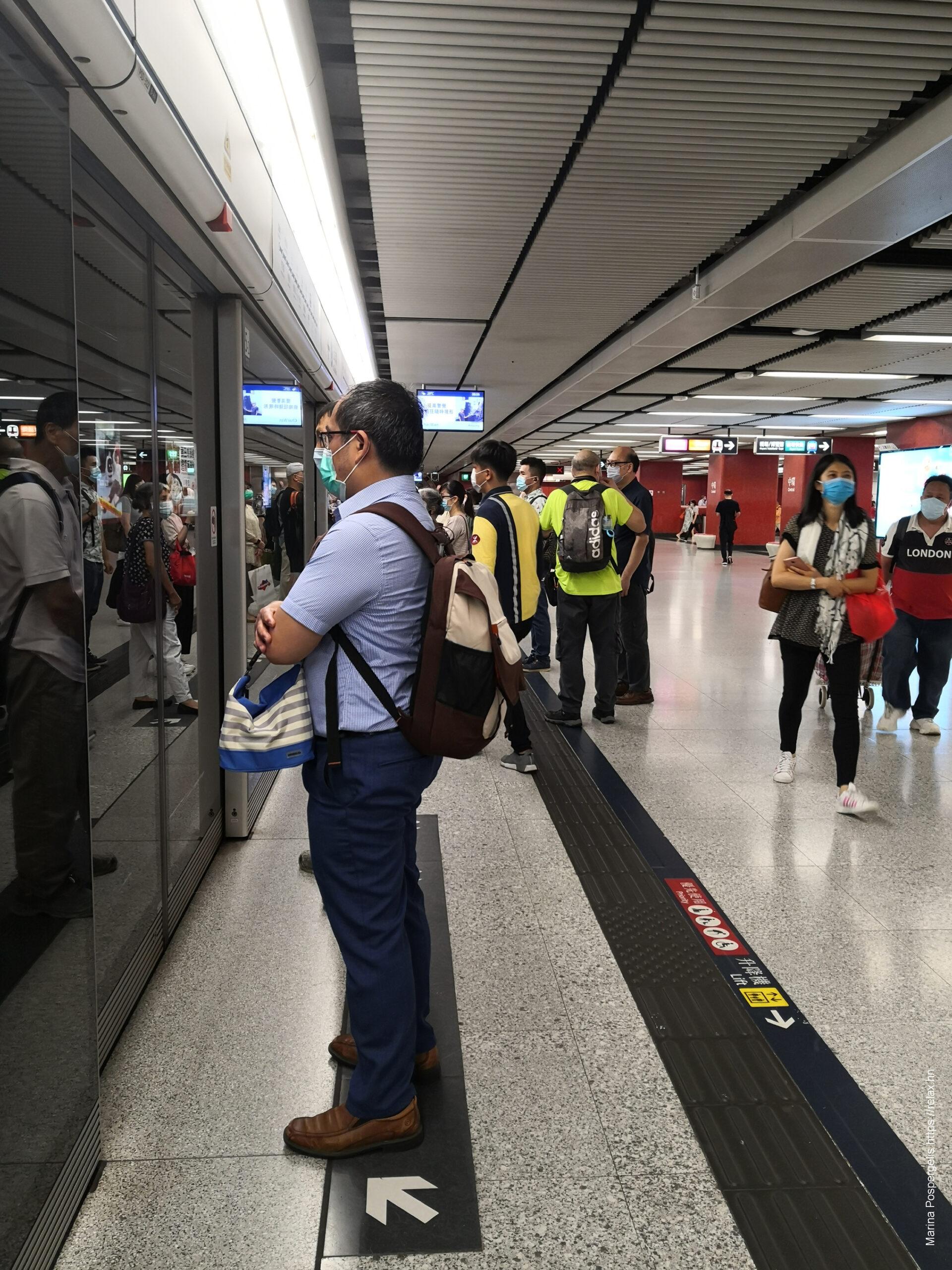Люди в метро ждут поезда в масках